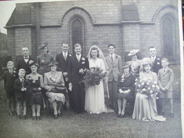 The photograph shows the marriage of Sidneys daughter Marjorie to James Newton. Sidney is shown on the photograph back row with Derek is son stood in front.